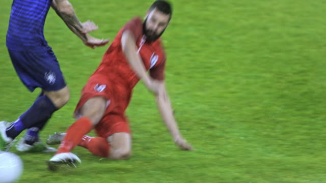 SLO MO Tackled soccer player falls to the ground
