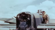 WS Tail gunner wearing flak vest climbing atop Lancaster bomber's fuselage and polishing Perspex of turret