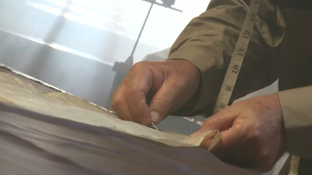 A tailor attaches a paper pattern to a piece of fabric. Available in HD.