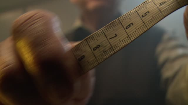 A tailor calculates a measurement. Available in HD.