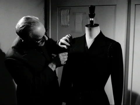 A tailor checks the stiching on a jacket