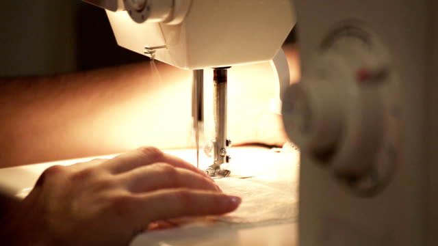 Tailor works with sewing machine