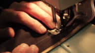 Tailor's hand using sweing machine. Man works on his small business tailoring suits.