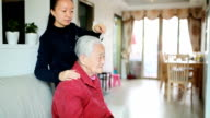 Taking care of senior woman combing