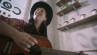 Talented female musician strums acoustic guitar and sings in local coffee shop.