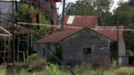 Tall grass grows out of control around an abandoned mill. Available in HD.
