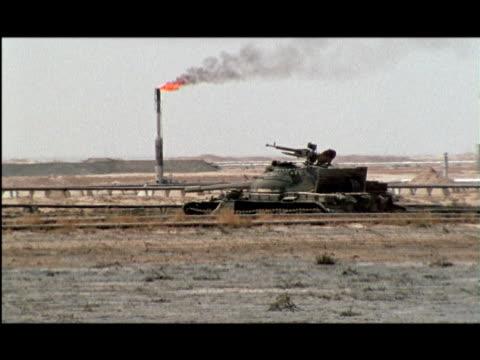 WS, ZI, MS, Tank abandoned in desert, burning oil well in background, Kuwait