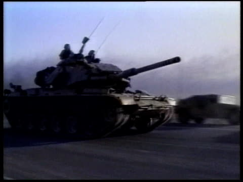 WS tank driving fast on road past stationary military vehicles