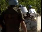 UN tank moves quickly down dusty road and negotiates road block Srebrnica Bosnia 1993