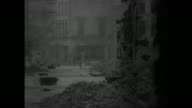 US tank moving down street / smoke pouring from burning buildings / building collapsing into street / German soldier crossing street / US soldiers...