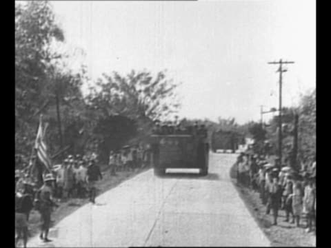 WS tank rides on street in Philippines during World War II as US soldiers walk and jeep carries others / montage troops and armored personnel...