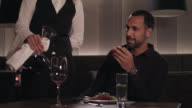 Tanned man with dark short hair and trimmed beard in classic black shirt with wrist watch sits in a hotel restaurant at a table in front of his dinner, blonde waitress in classic waiter clothing with bow-tie pours red wine out of a decanter in his glass.