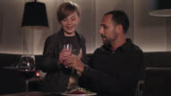 Tanned man with dark short hair and trimmed beard in classic black shirt with wrist watch sits in a stylish modern hotel restaurant at a table in front of his dinner, blonde young boy arrives asking for drinking water, 9 year old child drinks water.