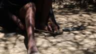 Tanzania, lake Eyasi, Hadzabe tribe, Datoga man stiffing and sharpening a metal arrow head