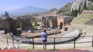 Taormina Greek Theatre aka Teatro Greco, tourist at the amphitheatre with Mount Etna Volcano behind, Sicily, Italy, Europe