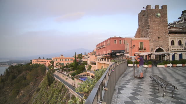 Taormina, the the Clock Tower and Mount Etna seen from Piazza IX Aprile on Corso Umberto, the main street in Taormina, Sicily, Italy, Europe