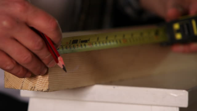 Tape measure with pencil on wood
