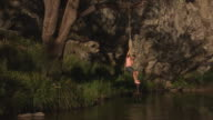 Tarzan rope swing hanging on tree on side of stream pan to Australian flag posted on a branch on a rock face and back / knot where rope is joined to...