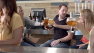 WS PAN tasting room at micro brewery as young couples holding beers in their hands reach out to greet each other by toasting / Thousand Palms, California, USA