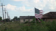 MS ZO Tattered American flag on fence blowing in wind in the Ninth Ward/ New Orleans, Louisiana