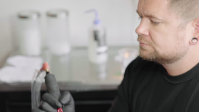 Tattoo Artist Concentrates on His Work