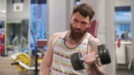 Tattooed and bearded man exercising at the gym
