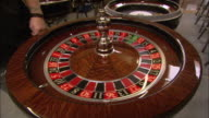 A tattooed croupier sets the white ball spinning on a roulette wheel.