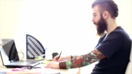 Tattooed hipster beard working in the office