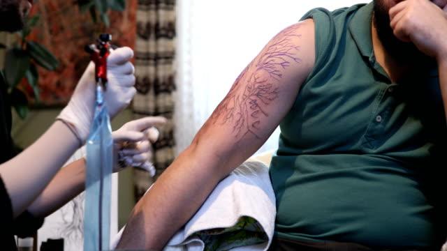 Tattooing a man in studio 4k