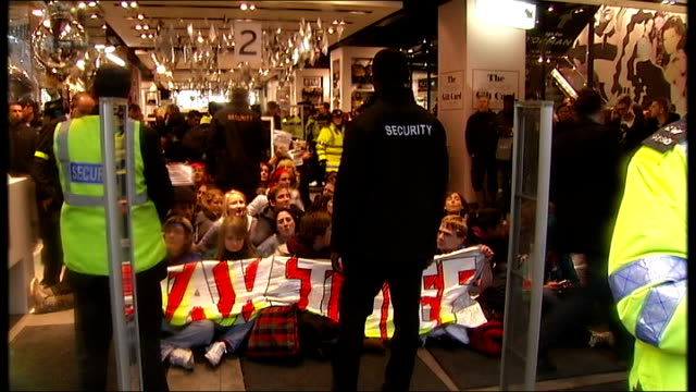 Tax avoidance protesters target Topshop flagship store in London ENGLAND London Oxford Street Close Shot of protest sign in street Group of...