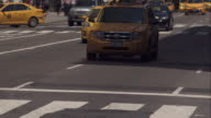 Taxi cabs and other auto traffic drive toward camera on busy street in New York City