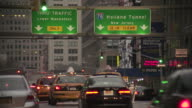 Taxi cabs and other communters in new york city traffic by the Holland Tunnel and lower manhattan early in the day