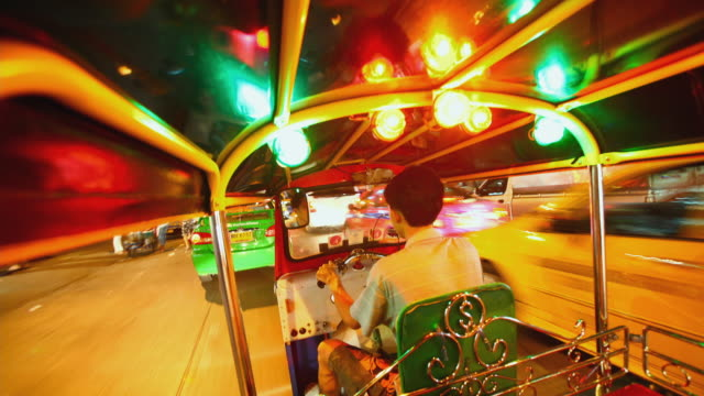 WS T/L POV Taxi driver driving tuk-tuk at night in the streets of Bangkok / Bangkok, Thailand