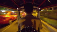 T/L MS POV Taxi driver getting in stationary Tuk Tuk then driving through city streets at night, Bangkok, Ayuthaya, Thailand