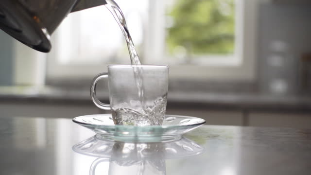 Tea preparation: pours boiled water from teapot into cup