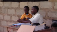 MS Teacher and school boy working with electrical components at desk outdoor, Tamale, Ghana