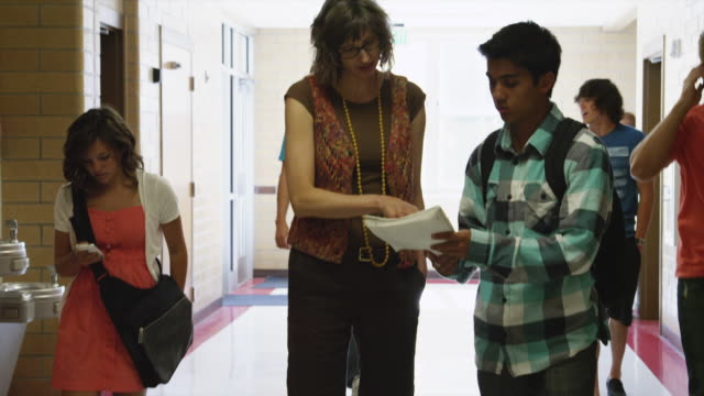 MS Teacher and student discussing papers in corridor / Spanish Fork City, Utah, USA