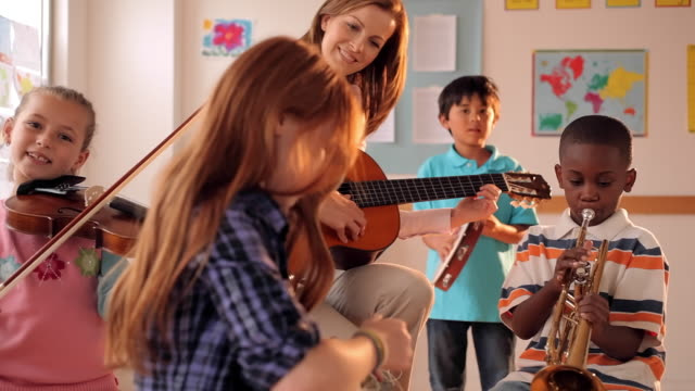 Teacher and students playing musical instruments