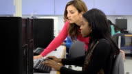 Teacher Assists Female Student in Computer Lab