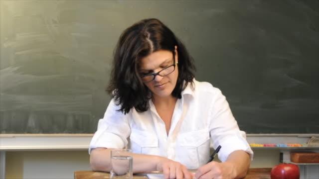 Teacher correcting exams in classroom