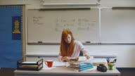WS ZO Teacher digging through big stack of paperwork on desk / Edmonds, Washington, USA