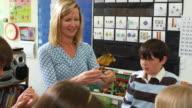 MS Teacher doing science demonstration, children (6-11) watching, Manchester, Vermont, USA