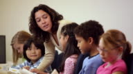 MS Teacher Helping Diverse Group of Young Students in School / Richmond, Virginia, USA