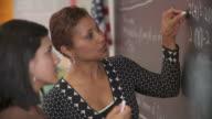 CU, Teacher helping student (14-15) at blackboard, Richmond, Virginia, USA,