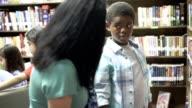 Teacher, mentor helps elementary-age boy select library book