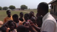 MS Teacher presenting solar power fan to children outdoors, Tamale, Ghana