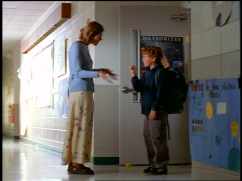 Teacher scolding red-haired boy with yoyo outside classroom