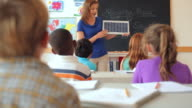 Teacher showing students solar panel in classroom