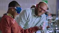Teacher supervises a student using Bunsen burner