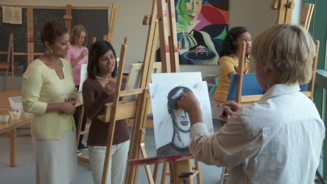MS, Teacher talking to student (14-15) drawing in art class, Richmond, Virginia, USA